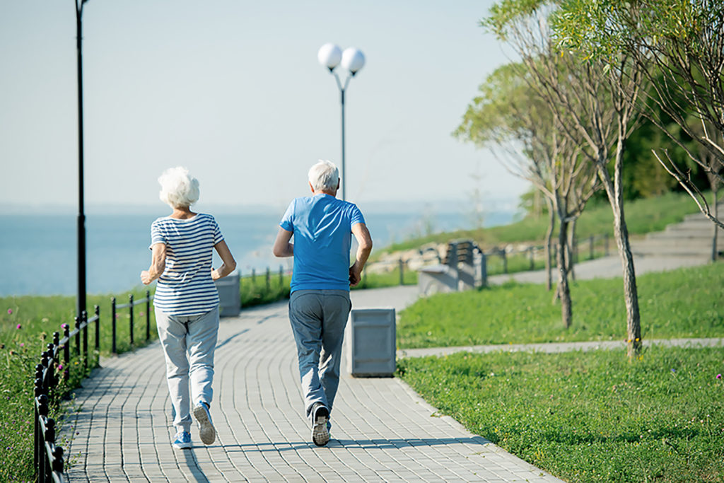 Back view portrait of active senior couple running on park lane along sea shore outdoors , copy space