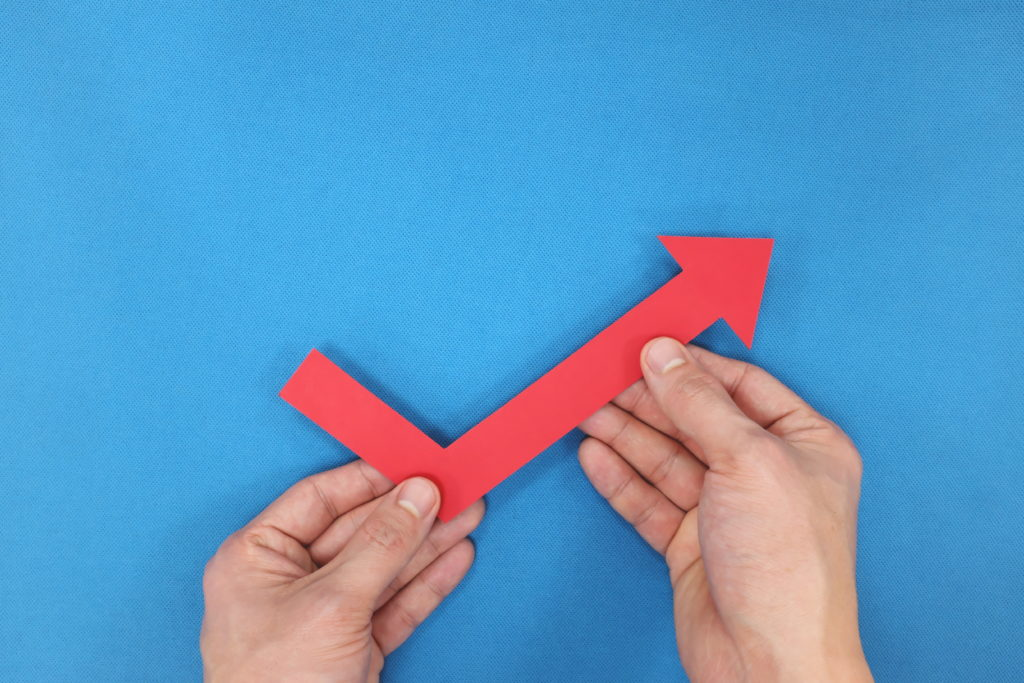 Economy and business rebound, bounce back and recovery concept. Hand holding red arrow going up.